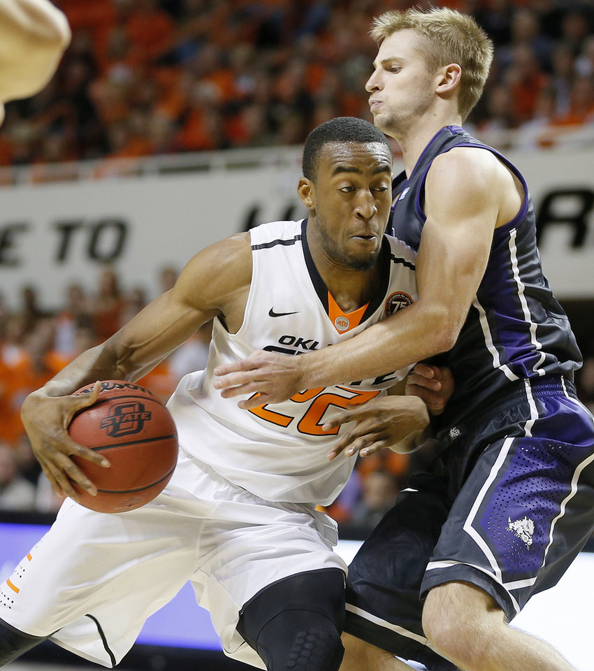 Photo - Oklahoma State's Markel Brown (22) tries to get past TCU's Christian Gore (13) during an NCAA college basketball game between Oklahoma State University (OSU) and TCU at Gallagher-Iba Arena in Stillwater, Okla., Wednesday, Jan. 15, 2014. Oklahoma State won 82-50. Photo by Bryan Terry, The Oklahoman