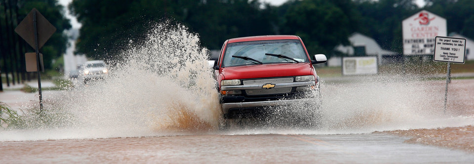 Photo - A truck sends large spray of  water as it makes it way through a flooded section of Hardesty Road, just west of US 177 after rain from Hurricane Bill produced localized flooding in areas of Pottawatomie County on Thursday, June 18,  2015.   Hardesty Road and US 177. Photo by Jim Beckel, The Oklahoman.