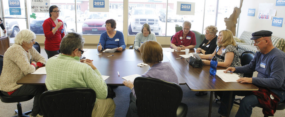 This photo taken on March 14, 2012 shows Tami Parker, standing left, a regional field director for the Obama campaign, instructing phone bank volunteers at a Obama campaign office in Lakewood, Colo. A handful of nurses and other volunteers took up their cell phones last week to call voters and talk up the health care overhaul. The volunteers were targeting elderly women. Holding up a sheet of talking points about the health law, campaign field director Tami Parker told about a dozen volunteers that the health care law faces a Supreme Court challenge later this month.