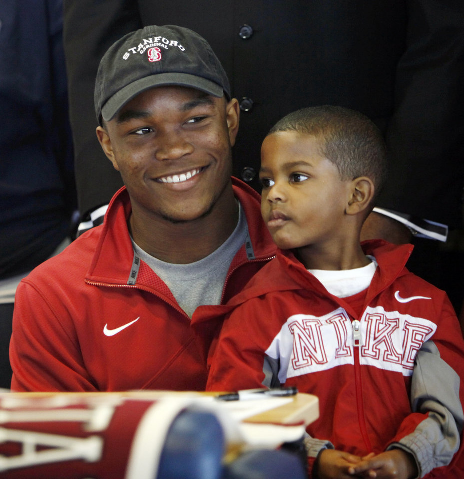 Photo - Heritage Hall's Barry J. Sanders smiles as he holds his brother Terrance Johnson, 4, during the National Signing Day ceremony at Heritage Hall in Oklahoma City, Wednesday, Feb. 1, 2012. Photo by Nate Billings, The Oklahoman