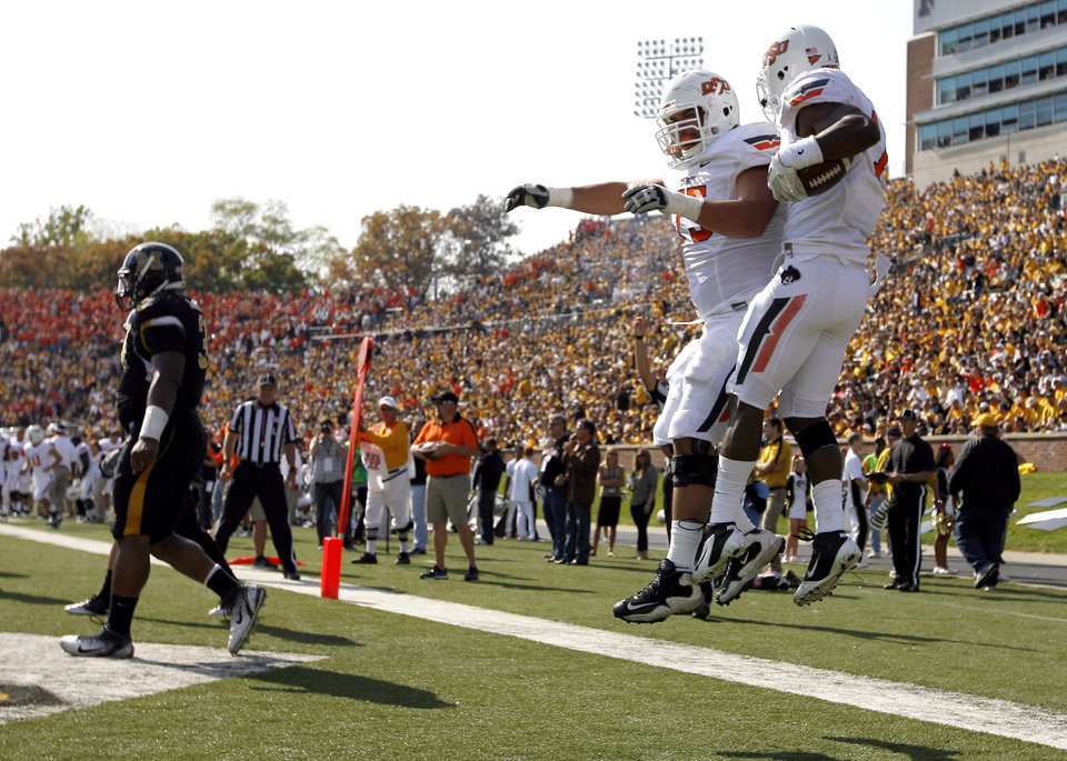 Oklahoma State's Joseph Randle (1) and Nick Martinez (75) celebrate a touchdown during a college football game between the Oklahoma State University Cowboys (OSU) and the University of Missouri Tigers (Mizzou) at Faurot Field in Columbia, Mo., Saturday, Oct. 22, 2011. Photo by Sarah Phipps, The Oklahoman
