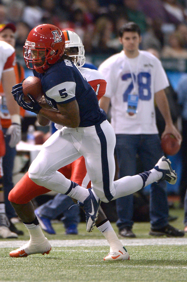 Photo - West defensive back Shaquille Richardson (5), of Arizona, intercepts a pass intended for East receiver Allen Hurns (1), of Miami, during the first half of the East-West Shrine Classic NCAA college football game in St. Petersburg, Fla., Saturday, Jan. 18, 2014. (AP Photo/Phelan M. Ebenhack)