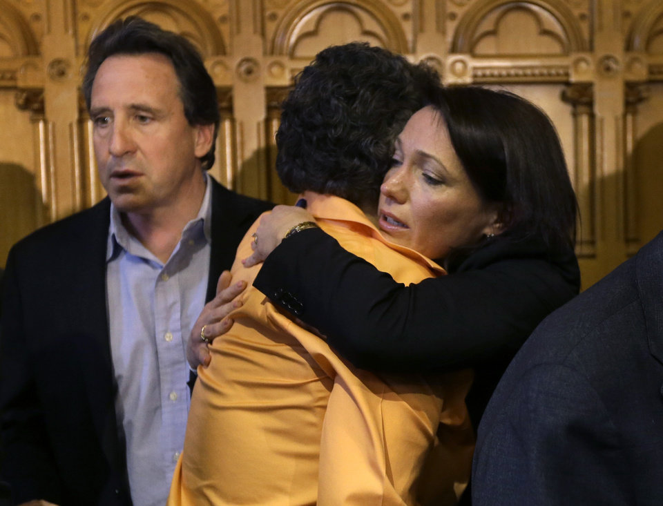 Photo - Nicole Hockley, right, mother of Sandy Hook School shooting victim Dylan Hockley, hugs Conn. state Sen. Beth Bye, D-West Hartford, center, as Neil Heslin, behind left, father of Sandy Hook shooting victim Jesse Lewis, looks on at the conclusion of legislation signing ceremonies at the Capitol in Hartford, Conn., Thursday, April 4, 2013. The legislation signed by Malloy adds more than 100 firearms to the state's assault weapons ban, sets eligibility rules for buying ammunition, and creates what officials have called the nation's first dangerous weapon offender registry. (AP Photo/Steven Senne)