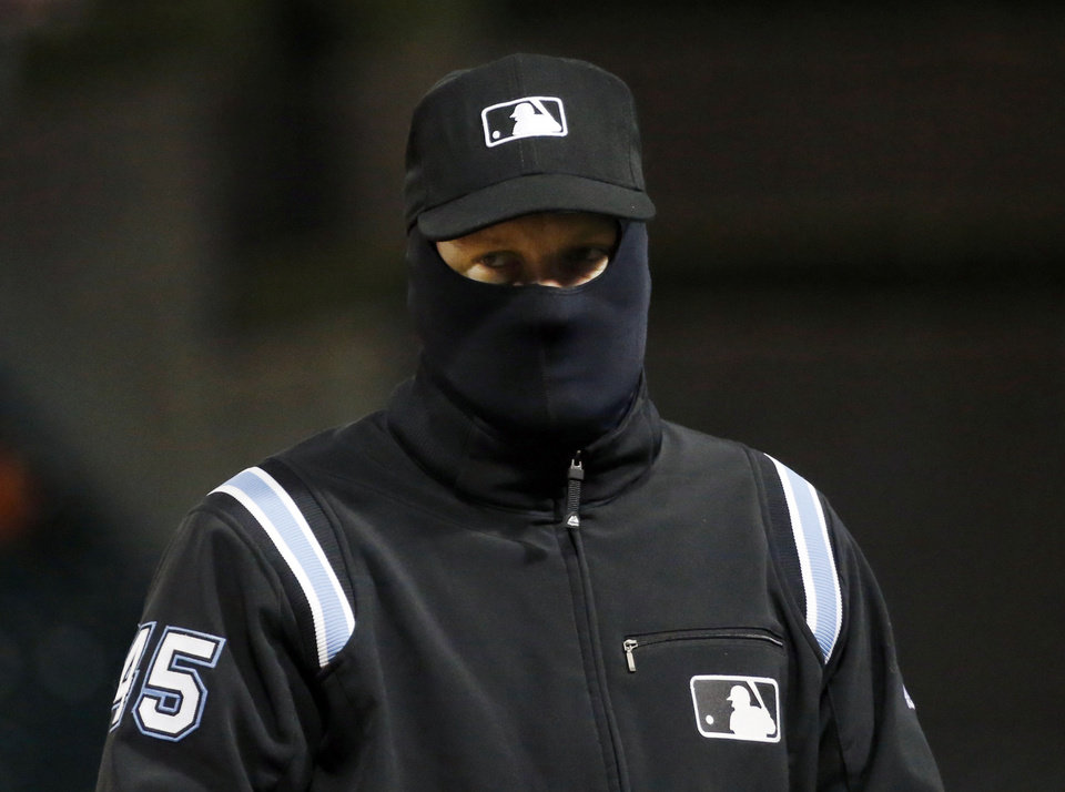Dressed for temperatures in the mid 30s, first base umpire Jeff Nelson looks out over the field during the third inning of a baseball game between the Chicago White Sox and the Seattle Mariners, Friday, April 5, 2013, in Chicago. (AP Photo/Charles Rex Arbogast)