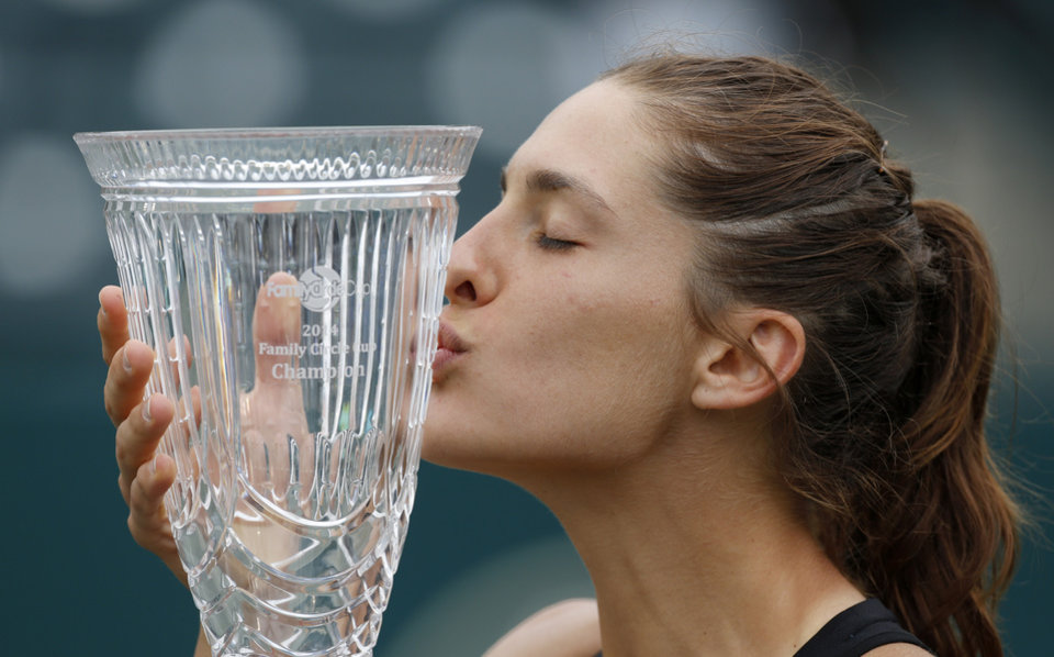 Photo - Andrea Petkovic, of Germany, kisses the trophy after defeating Jana Cepelova, of Slovakia, in two sets during the Family Circle Cup tennis tournament final in Charleston, S.C., Sunday, April 6, 2014. Petkovic won 7-5, 6-2 to win the championship. (AP Photo/Mic Smith)
