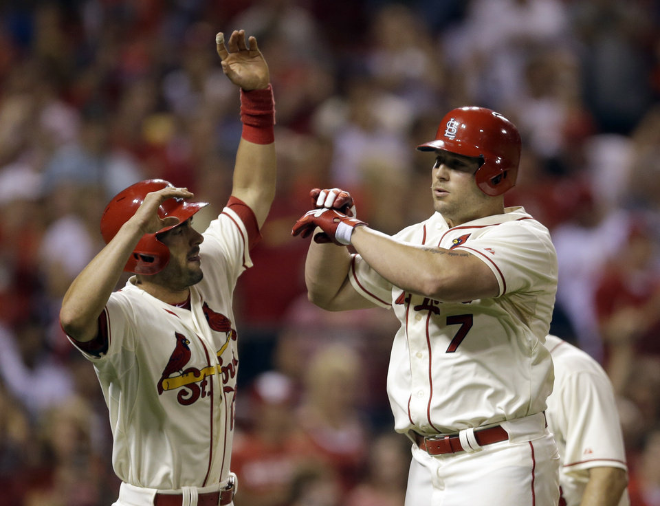 Photo - St. Louis Cardinals' Matt Holliday, right, is congratulated by teammate Matt Carpenter after hitting a three-run home run during the fifth inning in the second baseball game of a doubleheader against the Chicago Cubs Saturday, Aug. 30, 2014, in St. Louis. (AP Photo/Jeff Roberson)