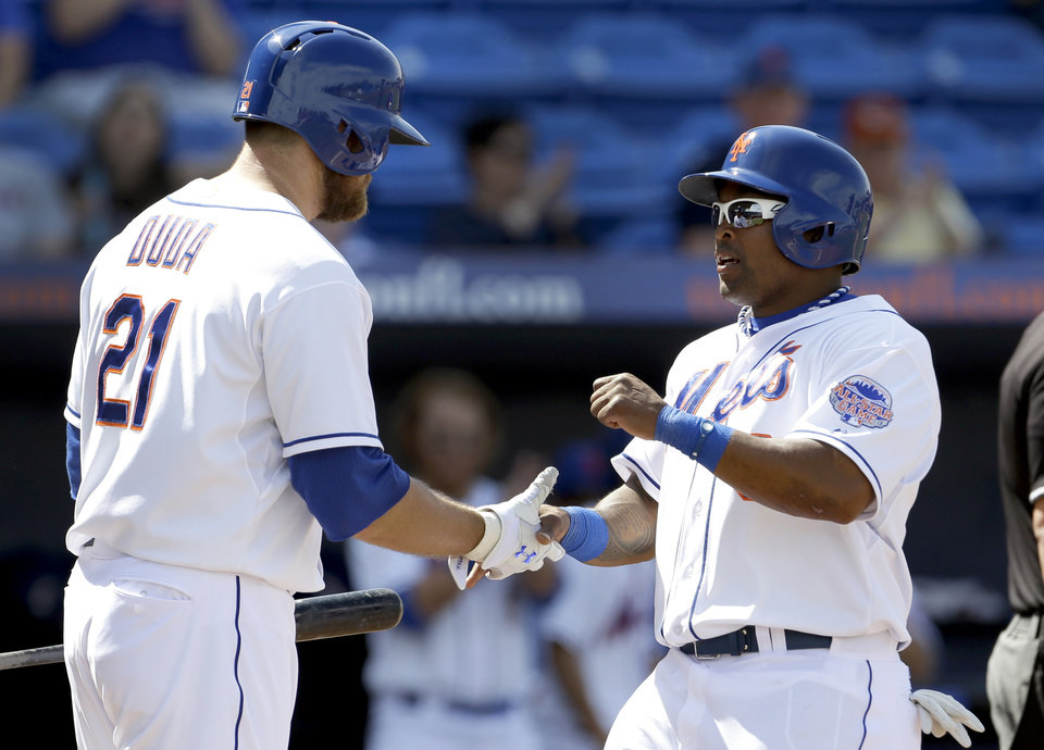 Photo - New York Mets' Marlon Byrd, right, is congratulated by teammate Lucas Duda after scoring on an RBI single by Ike Davis during the third inning of an exhibition spring training baseball game Saturday, March 9, 2013, in Port St. Lucie, Fla. (AP Photo/Jeff Roberson)