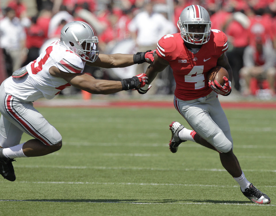 Photo - Ohio State running back Curtis Samuel, right, runs around the outside as linebacker Darron Lee defends during their spring NCAA college football game Saturday, April 12, 2014, in Columbus, Ohio. (AP Photo/Jay LaPrete)