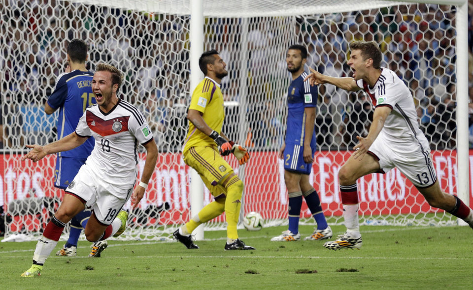 Photo - Germany's Mario Goetze, left, celebrates after scoring the opening goal during the World Cup final soccer match between Germany and Argentina at the Maracana Stadium in Rio de Janeiro, Brazil, Sunday, July 13, 2014. (AP Photo/Victor R. Caivano)