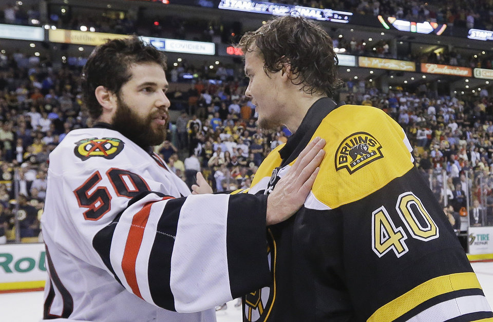 Photo - Chicago Blackhawks goalie Corey Crawford (50) is congratulated by Boston Bruins goalie Tuukka Rask (40), of Finland, after the Blackhawks beat the Boston Bruins 3-2 in Game 6 of the NHL hockey Stanley Cup Finals Monday, June 24, 2013, in Boston. (AP Photo/Elise Amendola)