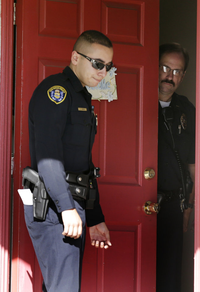 Photo - San Diego police officers stand in the doorway of the home of the mother of Colorado shooting suspect James Holmes Friday, July 20, 2012, in San Diego. A gunman in a gas mask barged into a crowded Denver-area theater during a midnight showing of the Batman movie on Friday, hurled a gas canister and then opened fire in one of the deadliest mass shootings in recent U.S. history. (AP Photo/Gregory Bull)  ORG XMIT: CAGB104