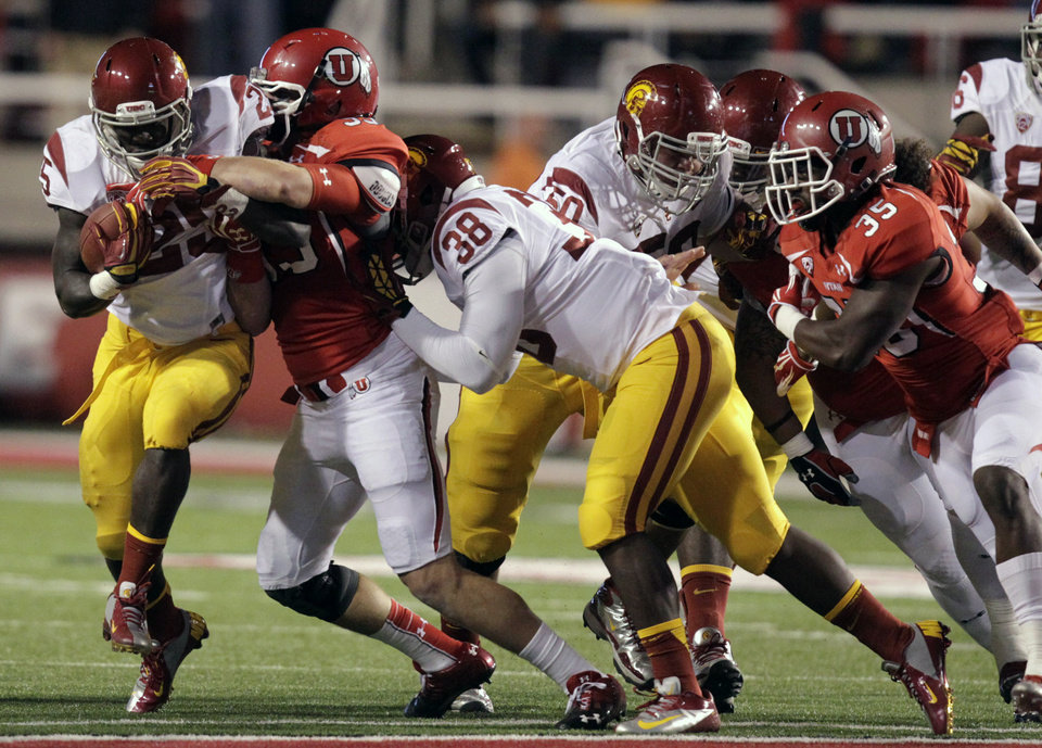 Photo -   Southern California running back Silas Redd, left, carries the ball as Utah defensive end Joe Kruger (99) makes a tackle while Southern California fullback Jahleel Pinner (38) blocks in the first quarter during an NCAA college football game on Thursday, Oct. 4, 2012, in Salt Lake City. (AP Photo/Rick Bowmer)