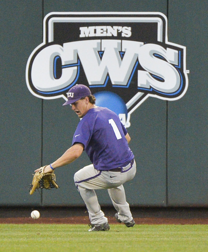 Photo - TCU Center fielder Cody Jones chases a ball hit for a double by Virginia's Branden Cogswell in the fifth inning of an NCAA baseball College World Series game in Omaha, Neb., Tuesday, June 17, 2014. (AP Photo/Ted Kirk)