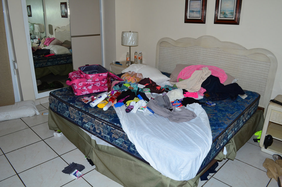 Photo - CORRECTS TYPE OF LODGING Clothes and toiletries are scattered on a bed in a bedroom of a high-rise condominium where famed drug boss Joaquin