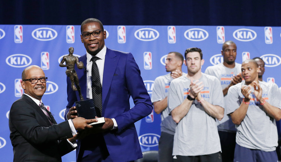 Photo - Oklahoma City Thunder's Kevin Durant, center, receives the MVP trophy from Percy Vaughn, of Kia, during a news conference announcing Durant as the winner of the 2013-14 Kia NBA Basketball Most Value Player Award in Oklahoma City, Tuesday, May 6, 2014. Durant's teammates applaud at right. (AP Photo/Sue Ogrocki)