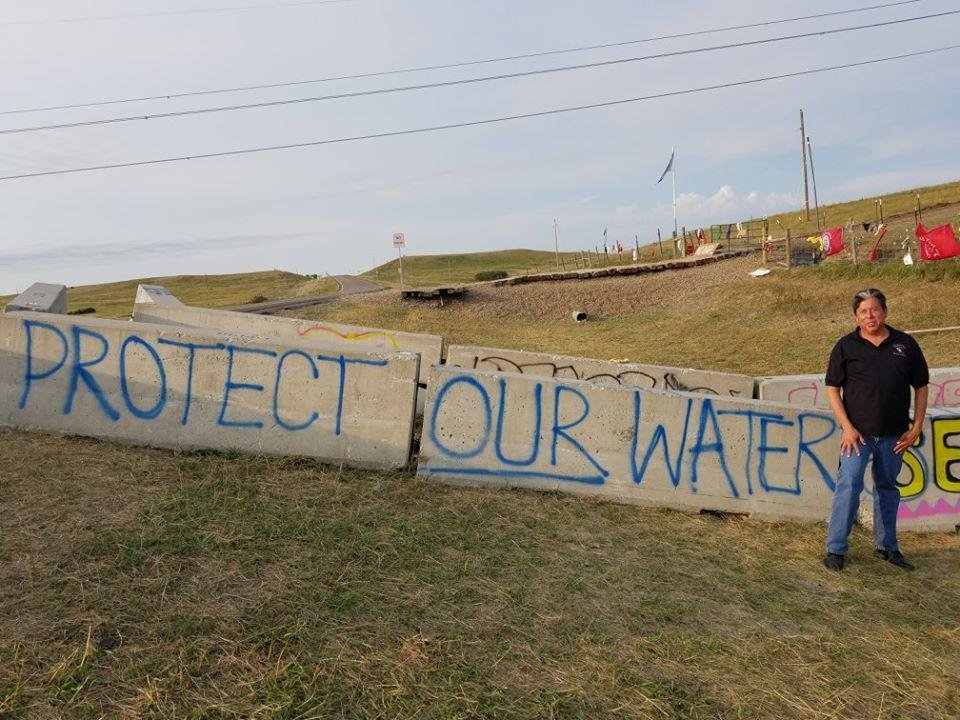 Photo -  The Rev. David Wilson, superintendent of the Oklahoma Indian Missionary Conference of the United Methodist Church, poses for a photo beside a concrete barrier near the Standing Rock Sioux Tribe protests in North Dakota. [Photo  provided]