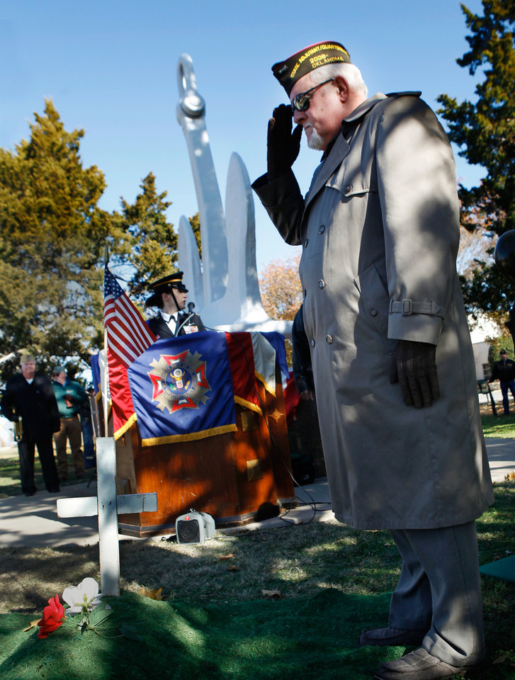 Photo - A placing a flower atop a symbolic grave, a veteran honors the dead at Pearl Harbor with a salute as part of a ceremony Wednesday, Dec. 7, 2011, near NW 13 and Broadway in Oklahoma City,  to commemorate the 70th anniversary of the Japanese attack on US forces at Pearl Harbor in 1941. The memorial was held  in front of the anchor salvaged  from the USS Oklahoma after it sank.  Morris    Photo by Jim Beckel, The Oklahoman