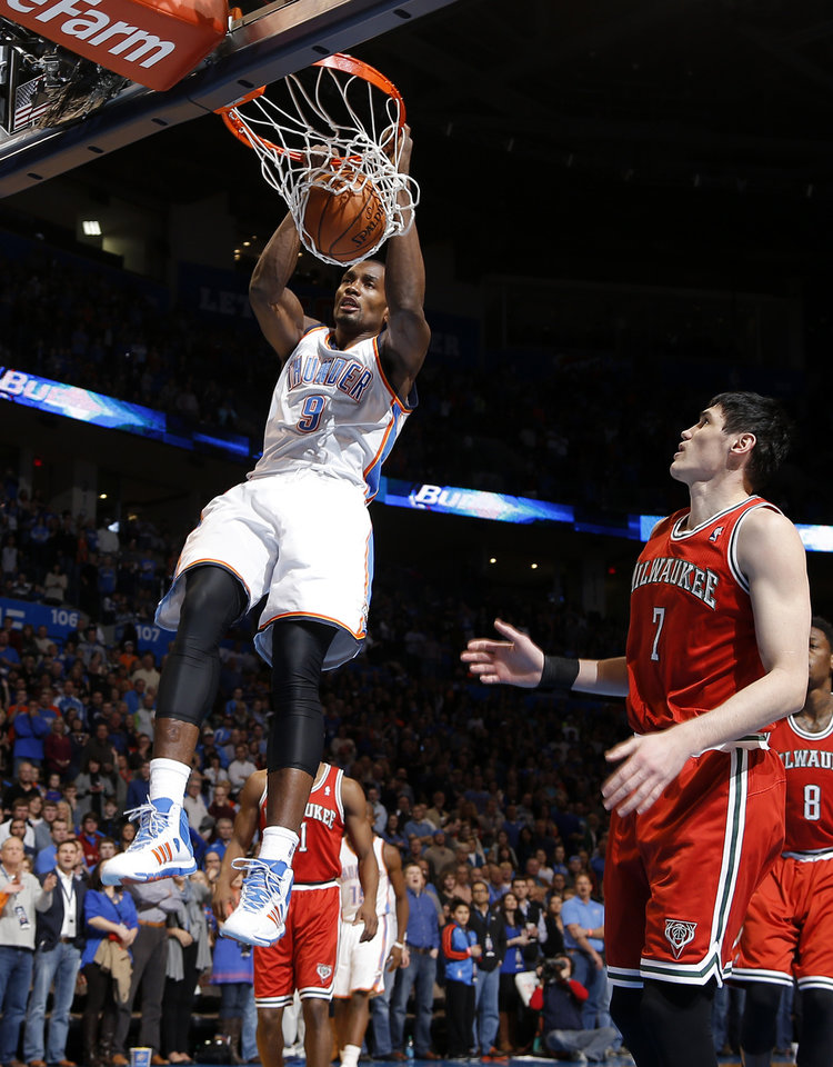 Oklahoma City's Serge Ibaka (9) dunks the ball beside Milwaukee's Ersan Ilyasova (7) during an NBA basketball game between the Oklahoma City Thunder and The Milwaukee Bucks at Chesapeake Energy Arena in Oklahoma City, Saturday, Jan. 11, 2014.  Photo by Bryan Terry, The Oklahoman