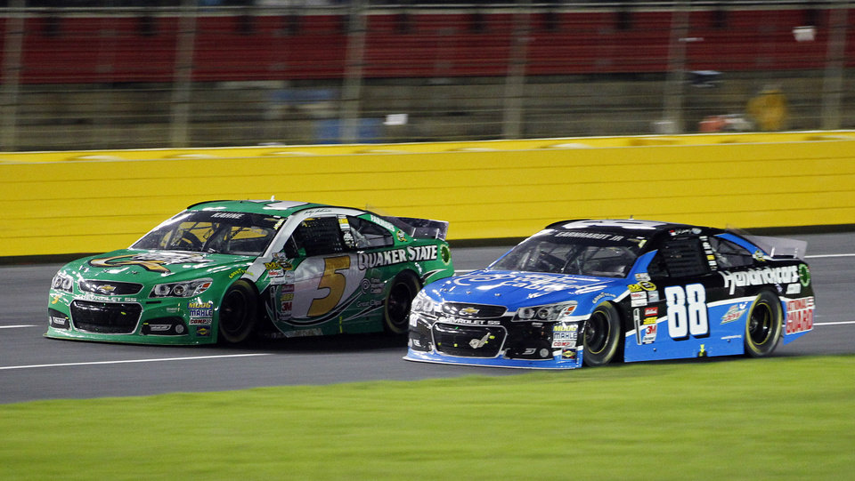 Photo - Kasey Kahne (5) and Dale Earnhardt Jr. (88) race on the front stretch during the NASCAR Sprint Cup Series auto race at Charlotte Motor Speedway in Concord, N.C., Saturday, Oct. 12, 2013. (AP Photo/Terry Renna)
