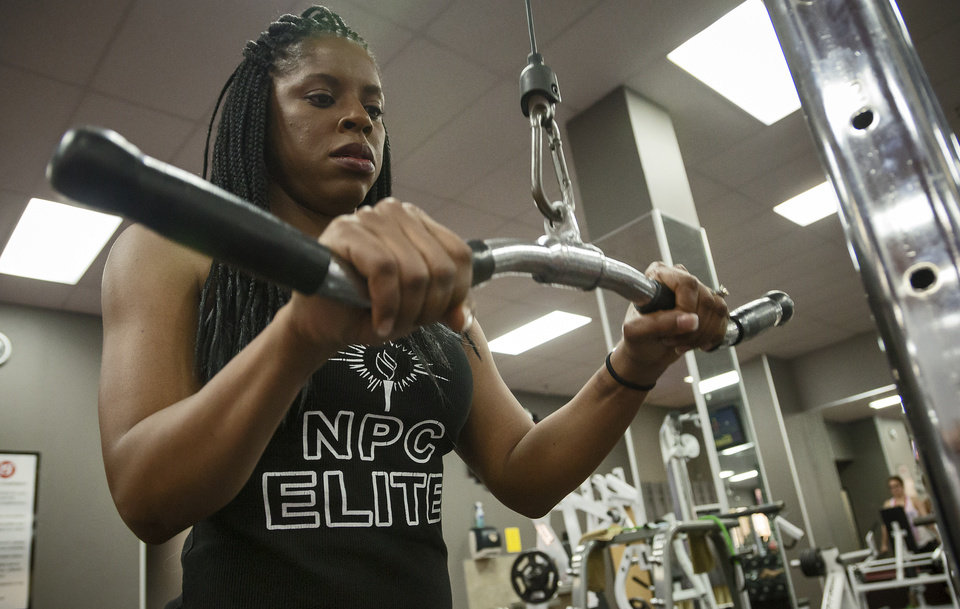 Photo -  Rhonda Spinks, a 36-year-old Oklahoma City resident, works out at the gym in OKC while lifting weights to prepare for a bodybuilding competition. Spinks who has competed in one body building competition, is determined to show how strong a cancer survivor can be by continue her pursuit of bodybuilding.    CHRIS LANDSBERGER -  CHRIS LANDSBERGER