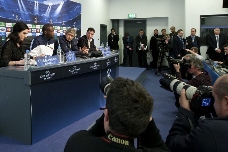 Photo - Manchester City's Manchester City's Yaya Toure, second left, and manager Manuel Pellegrini, centre left, answer questions during a press conference at the Etihad Stadium, Manchester, England, Monday Feb. 17, 2014. Manchester City will play Barcelona on Tuesday in a Champions League first knock out round soccer match. (AP Photo/Jon Super)