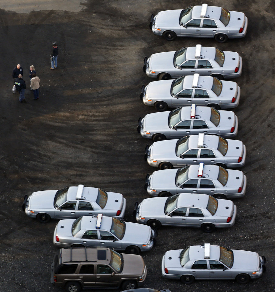 Police vehicles are lined up near a triage near Sandy Hook Elementary School in Newtown, Conn., where authorities say a gunman opened fire inside an elementary school in a shooting that left 27 people dead, including 18 children, Friday, Dec. 14, 2012. (AP Photo/Julio Cortez) ORG XMIT: CTJC109
