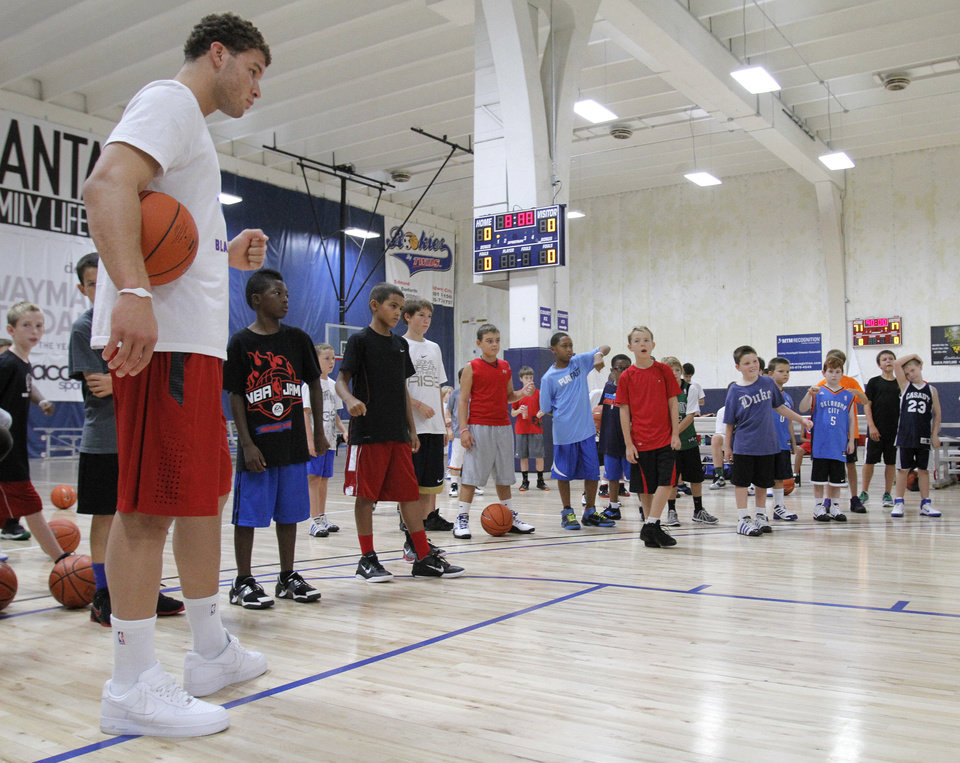 Photo - Blake Griffin gives camp participants advice during the Blake Griffin basketball camp at the Santa Fe Family Life Center in Oklahoma City Thursday, Aug. 4, 2011.  Photo by Garett Fisbeck, The Oklahoman