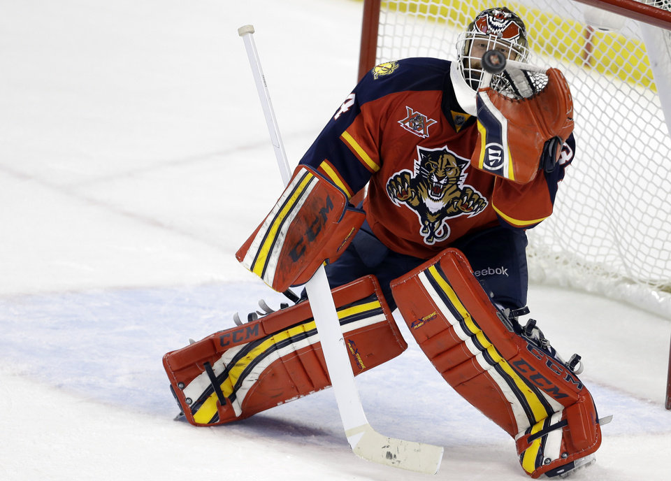 Photo - Florida Panthers goalie Tim Thomas stops the puck during the third period of an NHL hockey game against the New York Islanders, Tuesday, Jan. 14, 2014, in Sunrise, Fla. The Panthers defeated the Islanders 4-2. (AP Photo/Lynne Sladky)