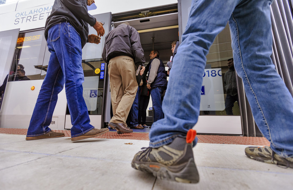 Photo - People board the streetcar at the Century Center stop for a free ride during the grand opening celebration day of the Oklahoma City streetcar system in downtown Oklahoma City, Okla. on Friday, Dec. 14, 2018. Photo by Chris Landsberger, The Oklahoman