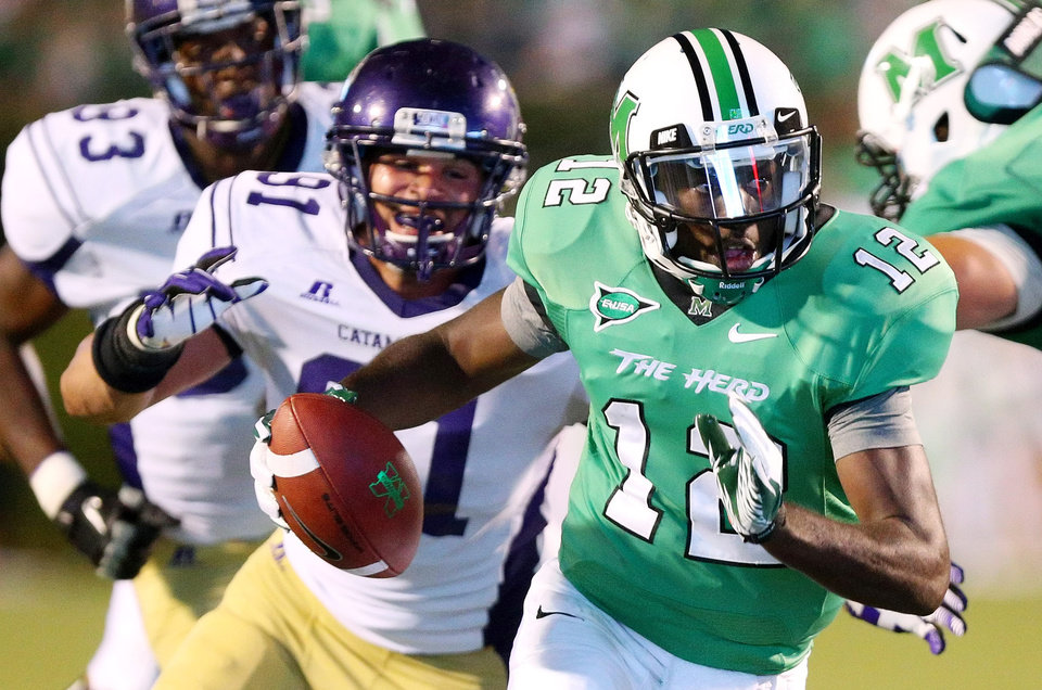 Photo - FILE - In this Sept. 8, 2012, file photo, Marshall's Rakeem Cato runs a quarterback keeper as Western Carolina defender Brian Johnson chases him during an NCAA college football game in Huntington, W.Va. Cato enters his senior season with the chance to become the most prolific quarterback in school history. (AP Photo/The Herald-Dispatch, Mark Webb, File)