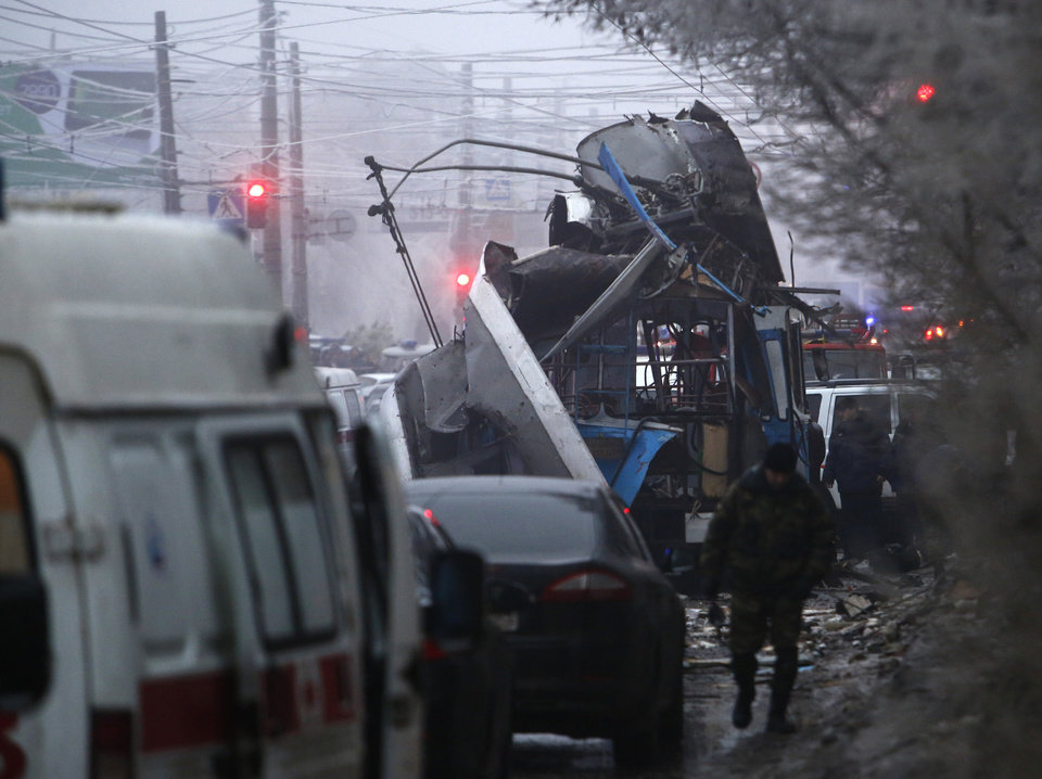 Photo - Experts and police officers examine a site of a trolleybus explosion, background, in Volgograd, Russia Monday, Dec. 30, 2013.  The explosion on the trolleybus left at least 10 people dead Monday, a day after a suicide bombing that killed at least 17 at the city's main railway. (AP Photo/Denis Tyrin)