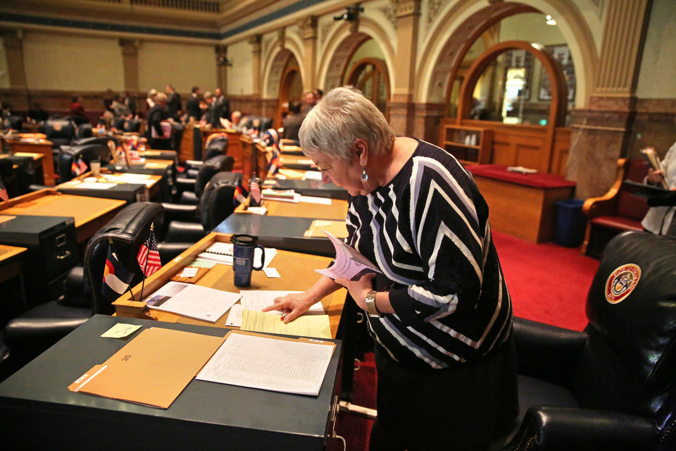 Photo - In this Jan. 22, 2014 photo, Colorado Democratic state senator Mary Hodge does some reading at her desk inside the chambers of the Colorado State Senate, at the Capitol, in Denver. Sen. Hodge has proposed a bill requiring better informing landowners and buyers about their property rights, which often doesn't include mineral rights below the surface. (AP Photo/Brennan Linsley)