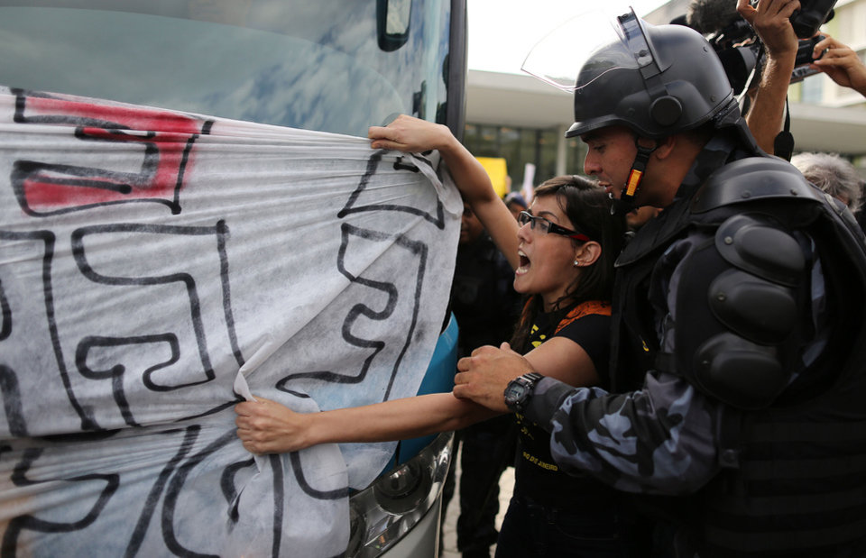 Photo - Demonstrators surround the bus carrying some members of Brazil's national soccer team from the airport to the Granja Comary training center, where the team will train and reside during the World Cup, in Rio de Janeiro, Brazil, Monday, May 26, 2014. Demonstrators are protesting the money being spent by the local government on the World Cup. (AP Photo/Leo Correa)