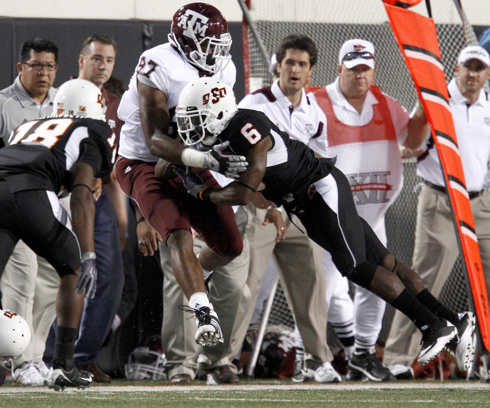 Photo - OSU's Andrew McGee brings down Texas A&M's Nehemiah Hicks during the college football game between Texas A&M University and Oklahoma State University (OSU) at Boone Pickens Stadium in Stillwater, Okla., Thursday, Sept. 30, 2010. Photo by Bryan Terry, The Oklahoman