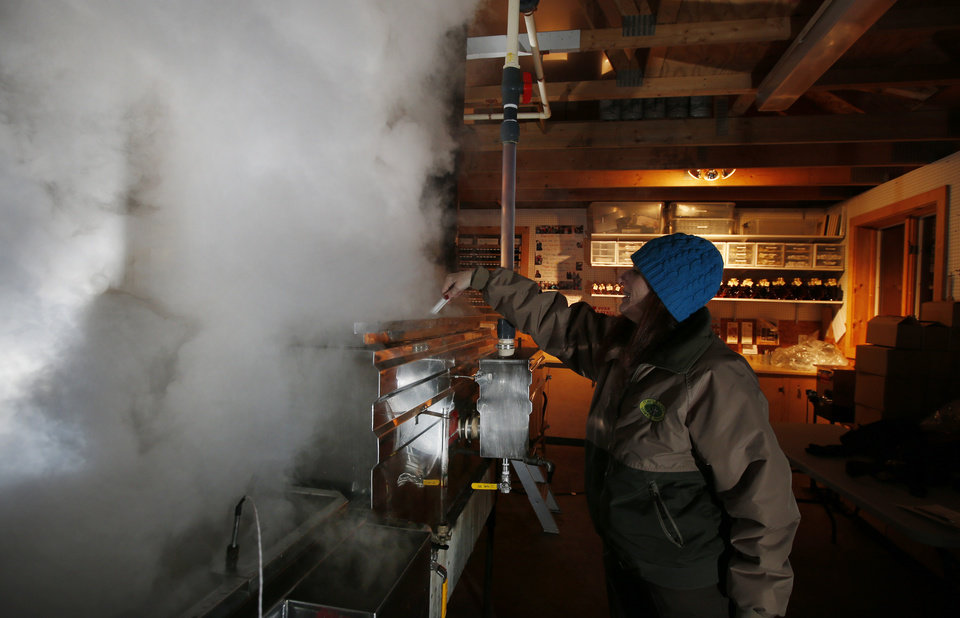Photo - In this March 13, 2014 photo, Kathy Gallagher makes sure sap doesn't boil over   in the evaporator at the Turtle Lane Maple sugar house in North Andover, Mass. It takes about 40 gallons of sap to yield one gallon of syrup. Maple syrup season is finally under way in Massachusetts after getting off to a slow start because of unusually cold weather. (AP Photo/Elise Amendola)
