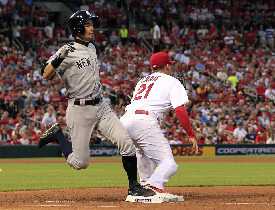 Photo - New York Yankees' Ichiro Suzuki, left, is safe at first as St. Louis Cardinals first baseman Allen Craig handles the throw during the third inning of a baseball game Wednesday, May 28, 2014, in St. Louis. Brian McCann scored on the play. (AP Photo/Jeff Roberson)