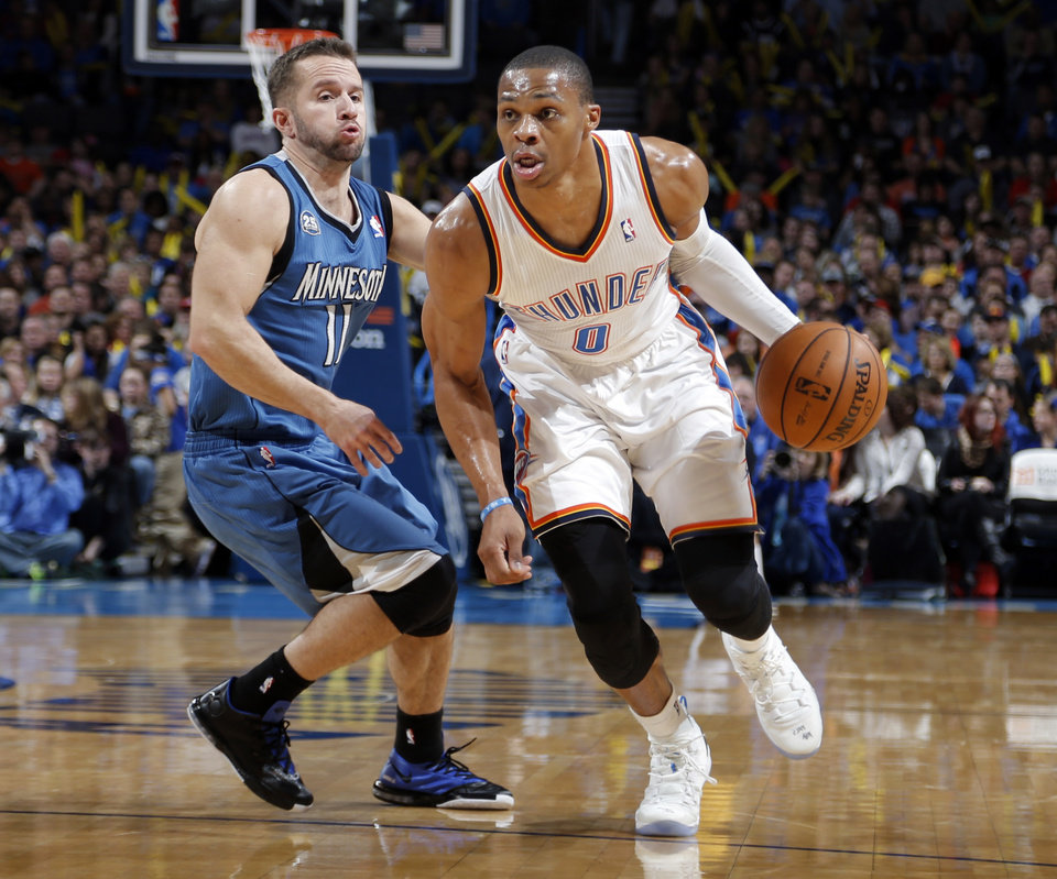 Photo - Oklahoma City's Russell Westbrook (0) drive past Minnesota's J.J. Barea (11) during the NBA game between the Oklahoma City Thunder and the Minnesota Timberwolves at the Chesapeake Energy Arena, Sunday, Dec. 1, 2013. Photo by Sarah Phipps, The Oklahoman