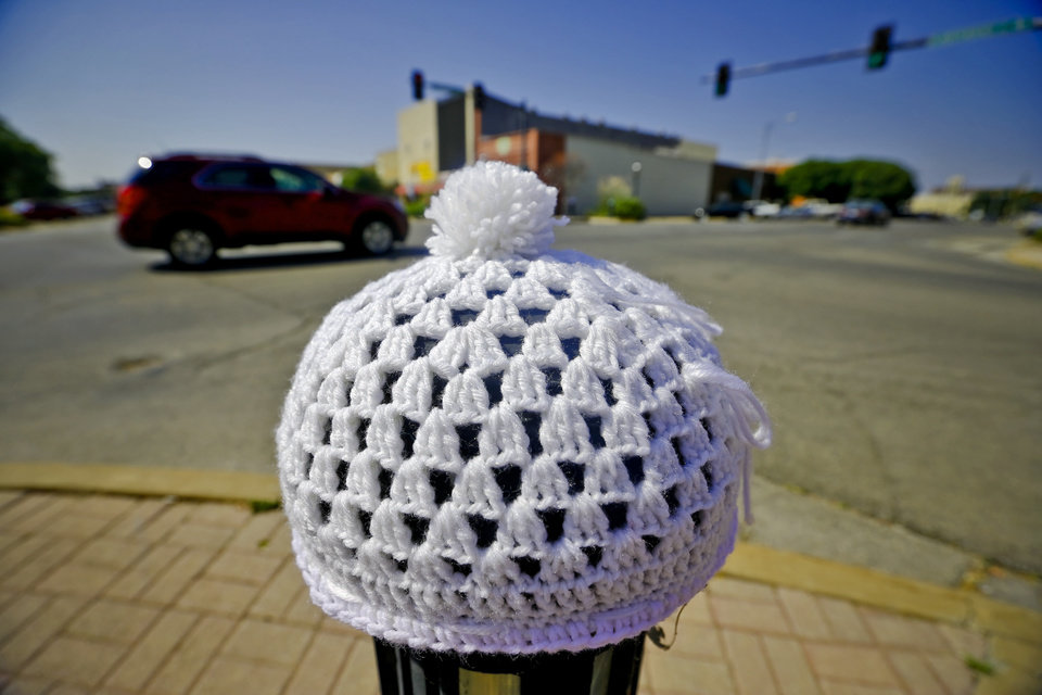 Photo - A knitted hats is attached to a sidewalk pole in the Enid town square as part of the Yarnover Enid community art event on Friday, Sept. 6, 2013 in Enid, Okla. The public art project was established to bring the town together to display 'art graffiti' created from items made and donated by the community.  Photo by Chris Landsberger, The Oklahoman