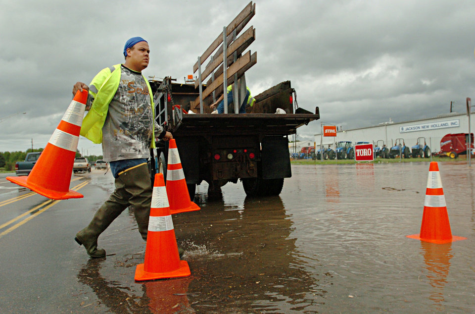 Photo - Eric Spencer blocks Highway 45 Bypass North at Ariways Boulevard in Jackson, Tenn. after the Forked Deer River spills over onto the road on Wednesday, April 27, 2011. (AP Photo/The Jackson Sun, Aaron Hardin)