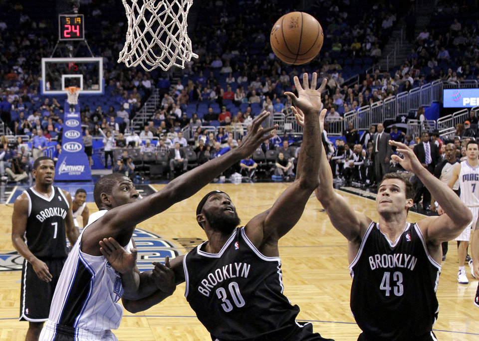 Photo - Orlando Magic power forward Andrew Nicholson, left, goes after a rebound against Brooklyn Nets' Reggie Evans (30) and Kris Humphries (43) during the first half of an NBA basketball game, Friday, Nov. 30, 2012, in Orlando, Fla. (AP Photo/John Raoux)