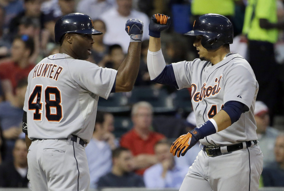 Photo - Detroit Tigers' Victor Martinez, right, celebrates with teammate Tori Hunter after hitting a solo home against the Chicago White Sox during the fifth inning of a baseball game in Chicago, Thursday, June 12, 2014. (AP Photo/Nam Y. Huh)