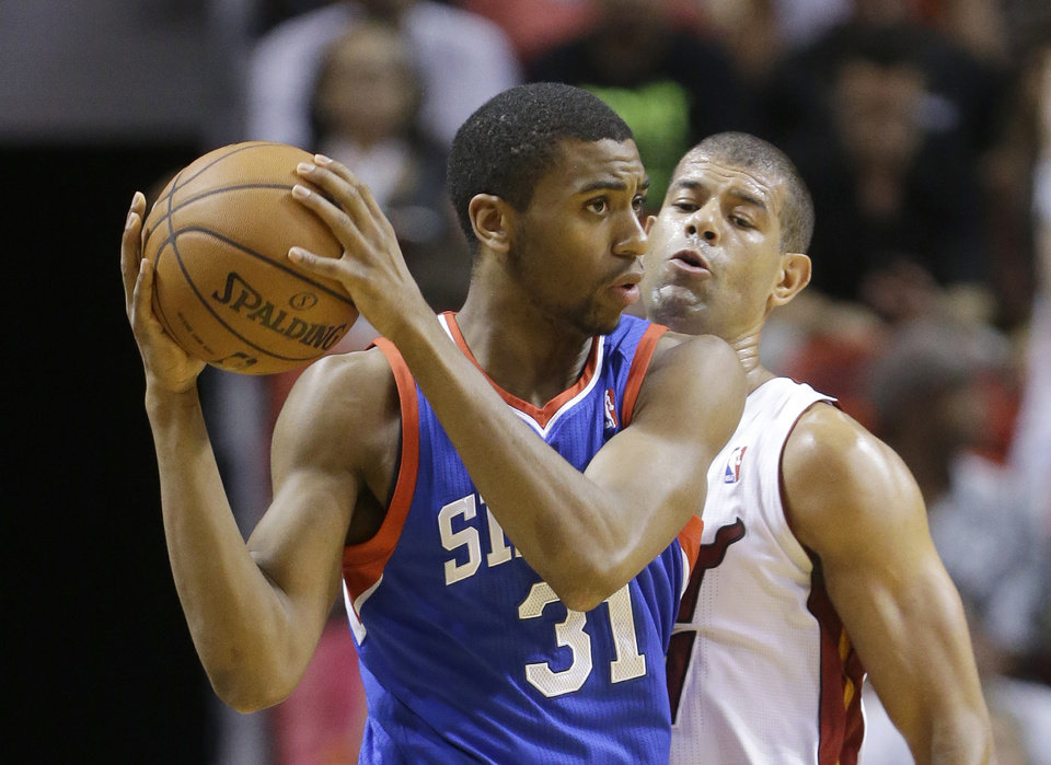 Photo - Philadelphia 76ers guard Hollis Thompson (31) looks for an opening past Miami Heat forward Shane Battier during the first half of an NBA basketball game on Wednesday, April 16, 2014, in Miami. (AP Photo/Wilfredo Lee)