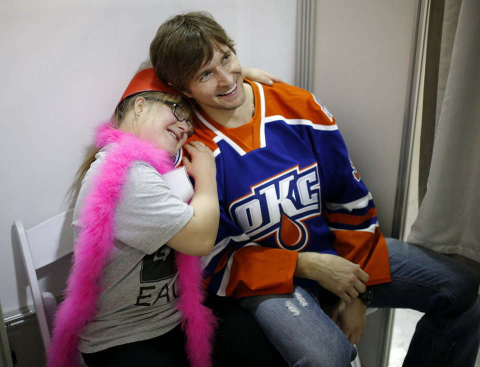 Photo - Sarah Shero, 15, poses for a photo in a photo booth with her Barons Buddy Denis Grebsehkov during a Barons Buddies event with the Oklahoma City Barons and Special Olympians in Oklahoma City, Tuesday, November 5, 2013. The Special Olympians and their families were introduced to the Barons player that they will paired with throughout the year. Photo by Bryan Terry, The Oklahoman