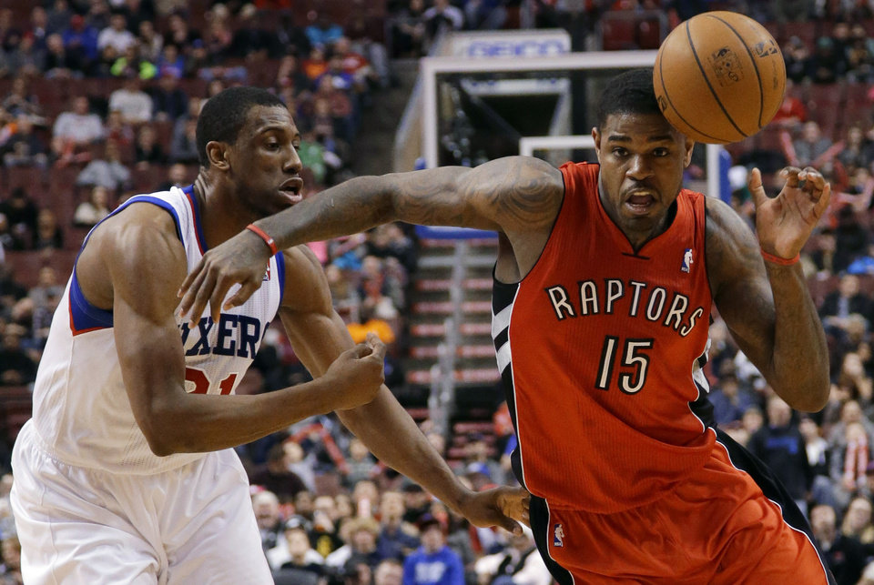 Photo - Toronto Raptors' Amir Johnson, right, loses the ball while trying to drive past Philadelphia 76ers' Thaddeus Young during the first half of an NBA basketball game, Friday, Jan. 24, 2014, in Philadelphia. (AP Photo/Matt Slocum)