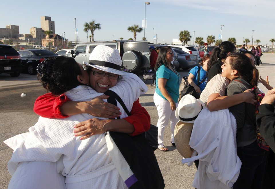 Patricia Wagner, right, hugs her sister Mercedes Perez de Colon,as their group is reunited after taking separate buses from Mobile, Ala., where the disabled Carnival ship Triumph docked, on Friday February 15, 2013 in Galveston, Texas. Hundreds of passengers opted to take an eight-hour bus ride to Galveston from Mobile.  Galveston is the home port of the ill-fated ship, which lost power in an engine-room fire Sunday some 150 miles off Mexico's Yucatan peninsula. (AP Photo/The Galveston County Daily News, Jennifer Reynolds) MANDATORY CREDIT