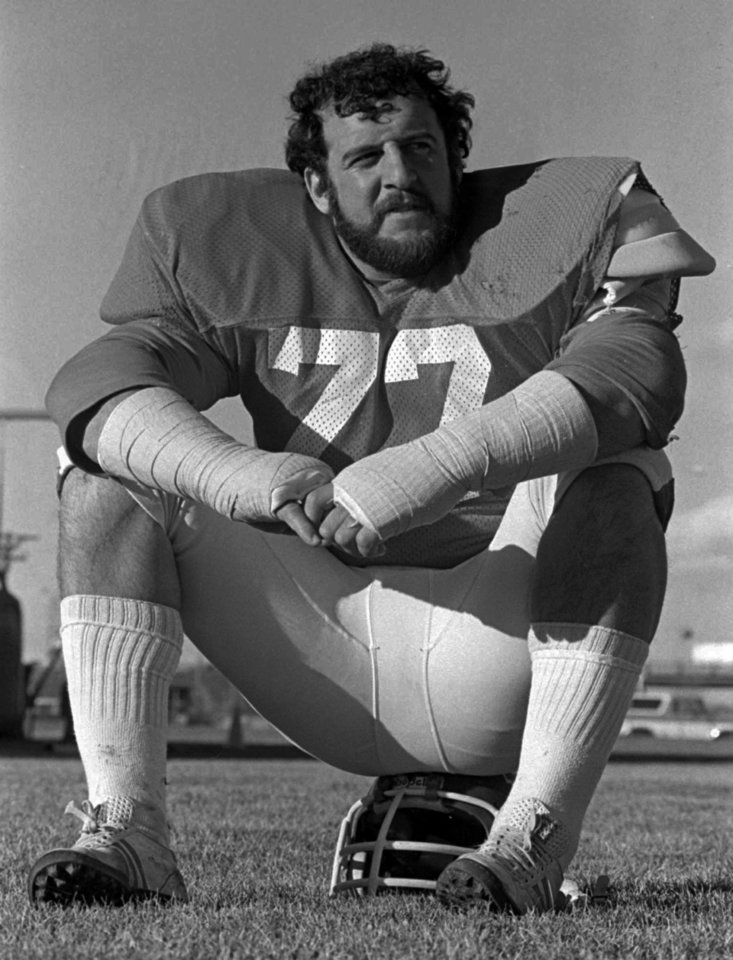 Photo - FILE - In this Nov. 25, 1977, file photo, Denver Bronco defensive lineman Lyle Alzado takes a break during practice as the NFL football team prepares to meet Baltimore. With uneven testing for steroids and inconsistent punishment, college football players are packing on significant weight _ in some cases, 30 pounds or more in a single year _ without drawing much attention from their schools or the NCAA in a sport that earns tens of billions of dollars for teams Football's most infamous steroid user was Alzado, who became a star NFL defensive end in the 1970s and 80s before he admitted to juicing his entire career. He started in college, where the 190-pound freshman gained 40 pounds in one year. It was a 21 percent jump in body mass, a tremendous gain that far exceeded what researchers have seen in controlled, short-term studies of steroid use by athletes. Alzado died of brain cancer in 1992.(AP photo)