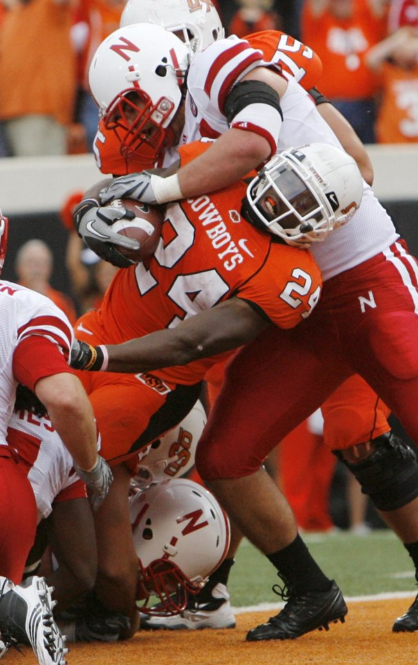 Photo - OSU's Kendall Hunter (24) rushes for a touchdown as Cameron Meredith (34) of Nebraska defends in the third quarter during the college football game between the Oklahoma State Cowboys (OSU) and the Nebraska Huskers (NU) at Boone Pickens Stadium in Stillwater, Okla., Saturday, Oct. 23, 2010. Nebraska won, 51-41. Photo by Nate Billings, The Oklahoman