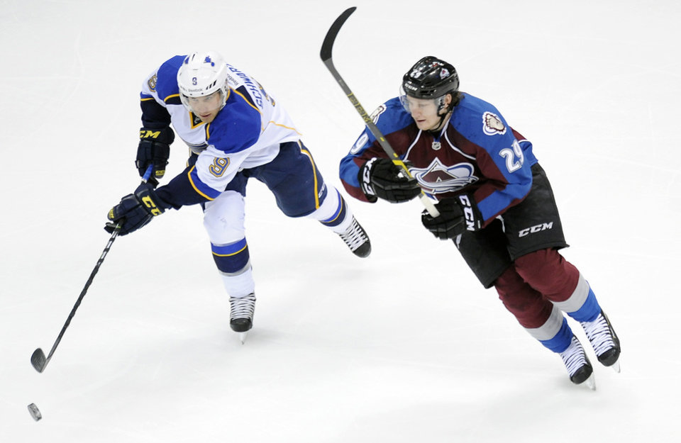 Photo - St. Louis Blues left wing Jaden Schwartz, left, fights for control of the puck with Colorado Avalanche center Nathan MacKinnon, right, in the first period of an NHL hockey game on Saturday, March 8, 2014, in Denver. (AP Photo/Chris Schneider)