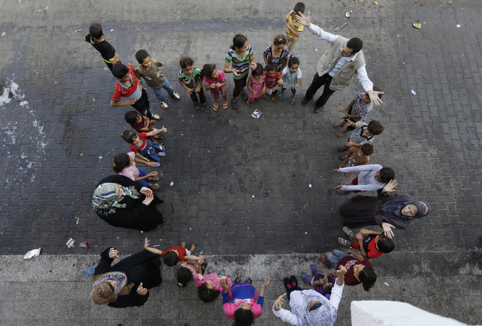 Photo - Volunteers lead a play session with displaced Palestinian children at a U.N. school where they had sought refuge along with their families during the war, in Gaza City, Gaza Strip, Thursday, Aug. 7, 2014. Taking advantage of the continuing ceasefire, volunteers from the local non-profit NGO 'Tomooh' (Ambition), arranged a special play session for children to try and lessen the stress they've been enduring after the weeks of conflict. In the playground the children got a chance to sing and play group games under the caring eye of volunteers. They hope that their efforts will lessen the damage of the traumatic recent weeks events, or at least help them forget for a short while. (AP Photo/Lefteris Pitarakis)