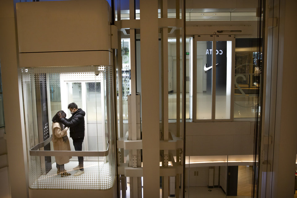 Photo -  In this Jan. 29 photo, a couple wearing face masks ride an elevator at a nearly empty shopping mall in Beijing. [Mark Schiefelbein/Associated Press File Photo]